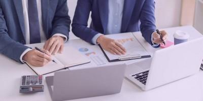 Imagem de mãos de duas pessoas com roupas sociais trabalhando em computadores com agendas