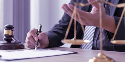 A imagem mostra um homem assinando um documento.