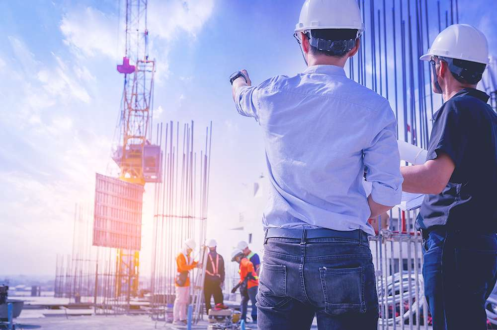 A imagem mostra dois homens que trabalham com construção civil apontando para uma máquina da obra.